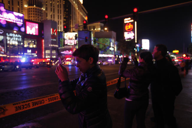 Bystanders watch as police investigate the scene of a crash on the Strip in Las Vegas that left one person dead and 37 injured after a car plowed into a group of pedestrians the evening of Sunday, ...