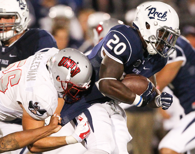 UNR's James Butler (20) is taken down by UNLV's Ryan McAleenan (56) during their football game at Mackay Stadium in Reno, Nev. on Saturday, Oct. 3, 2015. Chase Stevens/Las Vegas Review ...