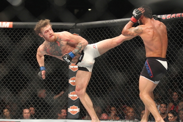Conor McGregor, left, lands a kick against Chad Mendes during their interim featherweight title bout at UFC 189 at the MGM Grand Garden Arena Saturday, July 11, 2015, in Las Vegas. McGregor won by ...