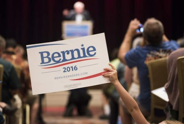 A supporter holds up a sign for U.S. Sen. Bernie Sanders as he speaks at Treasure Island hotel-casino in Las Vegas on Friday, June 19, 2015. Sanders is an independent from Vermont who is seeking t ...