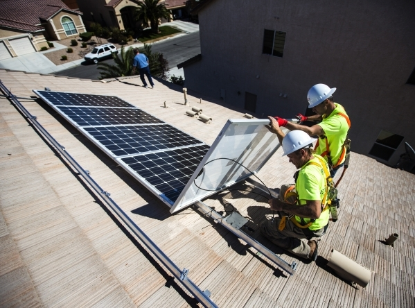 Jacy Sparkman, left, and Matt Neifeld with Robco Electric install solar panels at a home in northwest Las Vegas. (Jeff Scheid/Las Vegas Business Press)