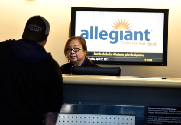 An Allegiant Air agent, left, assists a passenger at the check in counter at McCarran International Airport on Monday, April 27, 2015, in Las Vegas. (David Becker/Las Vegas Review-Journal)