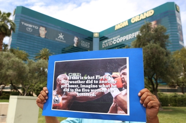 A protester, who refused to be identified, holds a sign as he protests against Floyd Mayweather ahead of his fight against Manny Pacquiao on May 1, 2015, in front of the MGM hotel-casino's m ...