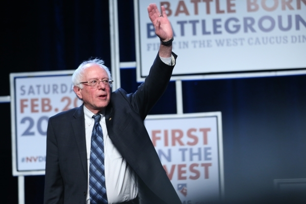 Democratic presidential candidate Bernie Sanders waves at supporters while on stage during the Battle Born/Battleground First in the West Caucus Dinner at the MGM Grand Conference Center on Wednes ...