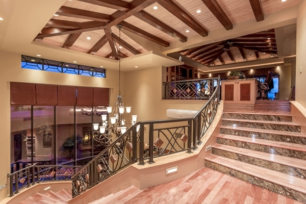 On the upper level of the home is one of its most exceptional areas — an enormous home office or den. It holds a gigantic, raised, double-desk platform, something essential for a couple like the ...