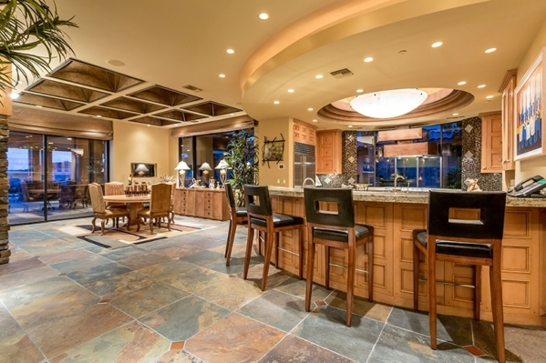 The gourmet-level kitchen features a wide, curving, marble-topped island. It can seat a half-dozen diners. COURTESY