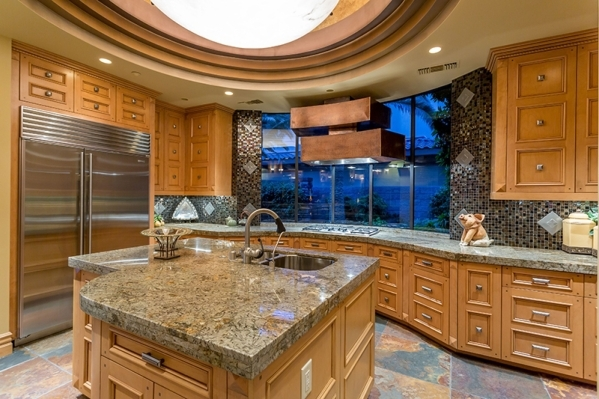The gourmet-level kitchen has a wide, curving, marble-topped island forms a functional separation between the areas. It can seat a half-dozen diners. Beyond, there is an island outfitted with a pr ...