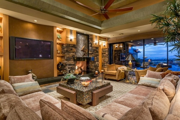 With an alcove ceiling and a large stone fireplace, the living room can accommodate extensive couches and free-standing seats, as well as a dedicated media center wall. It is sided by a northwest- ...