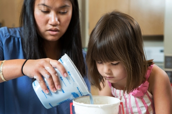 Katherine Lau, left, pours plaster into a mold of 4-year-old Hailey Dawson's hand while working in professor Brendan O'Toole's UNLV lab June 19, 2014. Aaron Mayes, UNLV Photo Ser ...