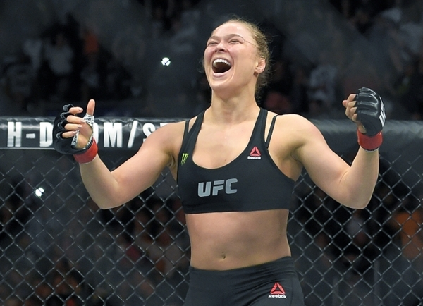 FILE - In this Feb. 28, 2015 file photo, Ronda Rousey, with Reebok insignia on her uniform, celebrates after defeating Cat Zingano in a UFC 184 mixed martial arts bantamweight title bout in Los An ...