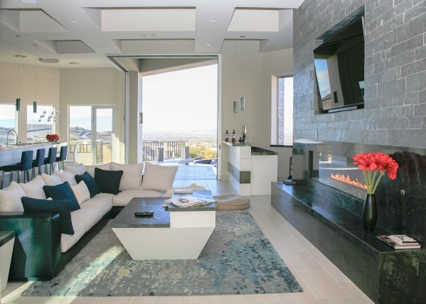 The living room features a large fireplace wall and wet bar with a pass-through window to the deck, a nice added convenience. ELKE COTE/REAL ESTATE MILLIONS