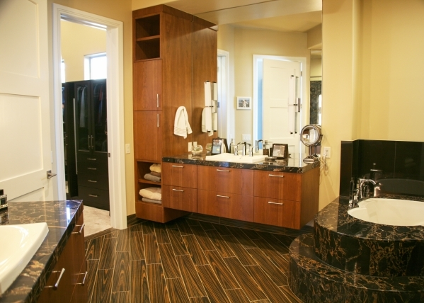 The master bath features a black pebble stone shower floor; split vanities with chocolate brown cabinets, and mirror-mounted chrome light fixtures. Its large walk-in closet has three levels of han ...