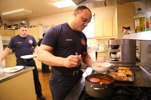 Firefighter Maco Woolard of the Clark County Fire Department station 28 serves himself tomato soup and paninis as Firefighter Chris Thorpe waits behind him in Summerlin, Wednesday, Dec. 30, 2015 i ...