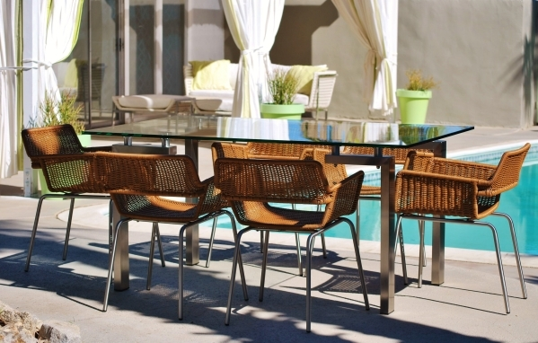 The Deepwell rectangular dining table by outside/in features a stainless steel with tempered glass top. It is paired with synthetic rattan dining chairs. COURTESY