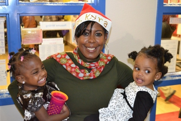Southern Nevada Children First employee Kyra Smith-Olson holds Aubrey Rose Fields, left, and Dilyn Mehari during the nonprofit organizationþÄôs annual holiday party. Bank of Nevada employ ...