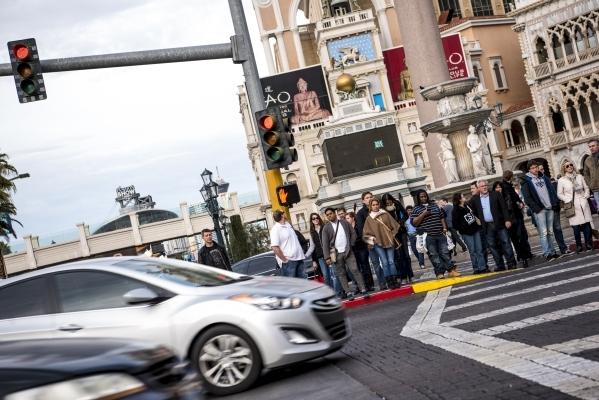 Pedestrians wait to cross the road in front the Venetian hotel-casino in Las Vegas on Sunday, Jan. 3, 2015. Joshua Dahl/Las Vegas Review-Journal