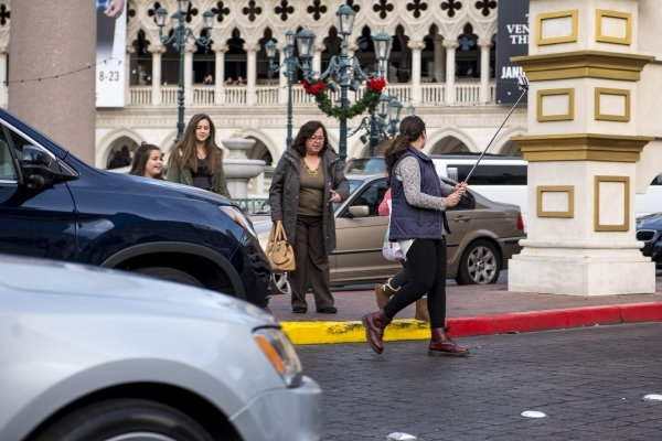 A  young girl with a selfie stick walks in front of cars entering the Venetian hotel-casino in Las Vegas on Sunday, Jan. 3, 2015. Joshua Dahl/Las Vegas Review-Journal