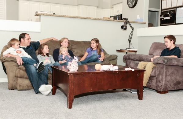 The Scow family, from left, Spencer, 3, Brad, father, Jane, 7, Julie, mother, Macy, 1, and Bailey, 10, talk during the lesson presented by Caleb, 13, right, on Family Night at their Las Vegas home ...