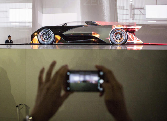 A Faraday Future executive takes a photo of the FFZero1 prototype during the unveiling event at the Las Vegas Village Lot, 3901 Las Vegas Boulevard South on Monday, Jan. 4, 2016. Faraday is schedu ...