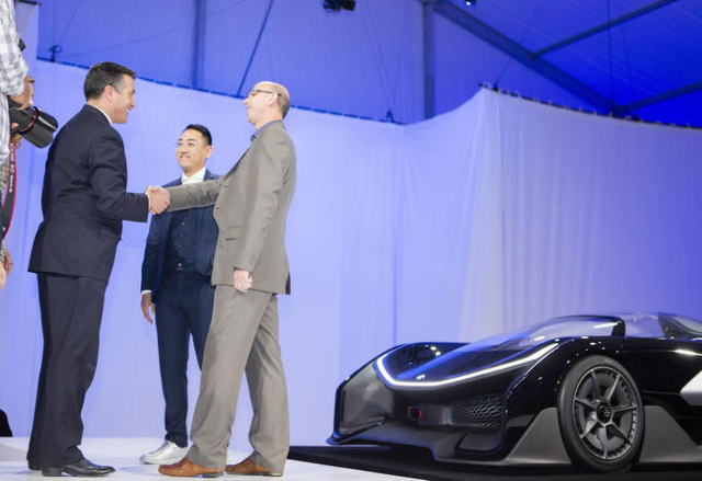 Nevada Gov. Brian Sandoval, left, shakes hands with Faraday Future executive Nick Sampson while Faraday's Richard Kim looks on during the unveiling of the FFZero1 prototype at Las Vegas Vill ...