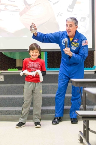 Former NASA astronaut Dr. Don Thomas works with McMillan Elementary third grader Carlos, 8, on a gravity experiment during his presentation at the Las Vegas Las Vegas on Wednesday, Jan. 6, 2016. D ...