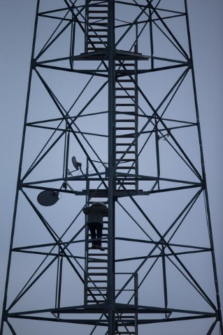 An anti-government protestor climbs down from a watch tower near by the entrance of Malheur National Wildlife Refuge headquarters, which is occupied by the group, near Burns, Ore. on Monday, Jan.  ...