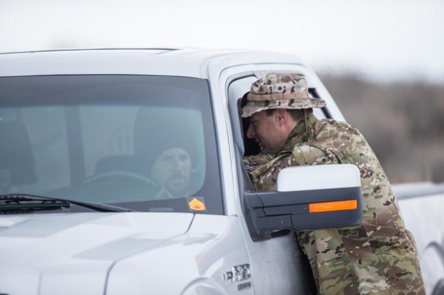 Anti-government protestors stand guard by the entrance of Malheur National Wildlife Refuge headquarters, which they are occupying, near Burns, Ore. on Monday, Jan. 4, 2016. The protestors, many of ...