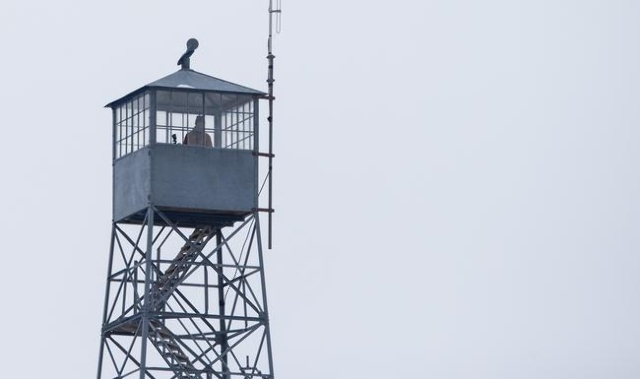 An anti-government protestor stands in a watch tower near by the entrance of Malheur National Wildlife Refuge headquarters, which is occupied by the group, near Burns, Ore. on Monday, Jan. 4, 2016 ...