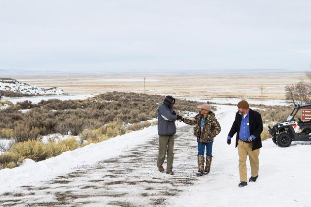 Arizona rancher LaVoy Finicum, center, greets a fellow anti-government protestor as Jason Patrick walks at the Malheur National Wildlife Refuge headquarters, which is occupied by the group, near B ...