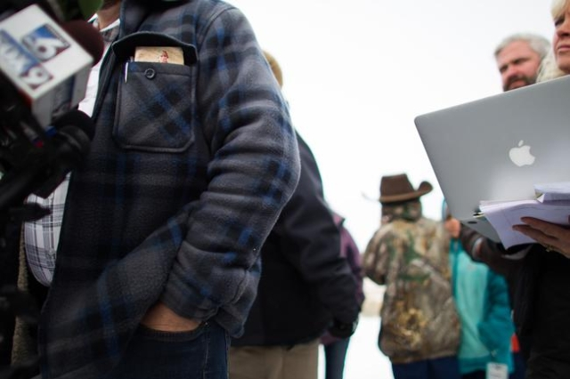 Ammon Bundy, with a copy of the U.S. constitution in his pocket, speaks with reporters at a news conference by the entrance of Malheur National Wildlife Refuge near Burns, Ore. on Monday, Jan. 4,  ...