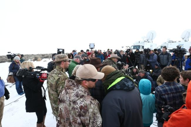 Anti-governments protestors speak with one another as LaVoy Finicum, an Arizona rancher, center right, speaks with reporters at a news conference by the entrance of Malheur National Wildlife Refug ...