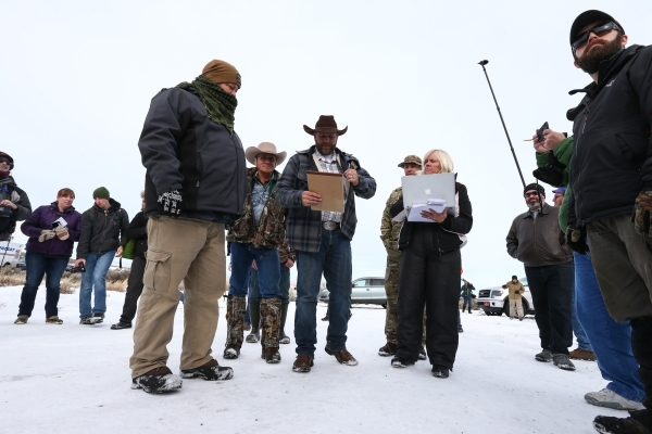 Ammon Bundy, center, prepares to speak with reporters at a news conference by the entrance of Malheur National Wildlife Refuge near Burns, Ore., on Monday, Jan. 4, 2016. Bundy, who is the son of N ...