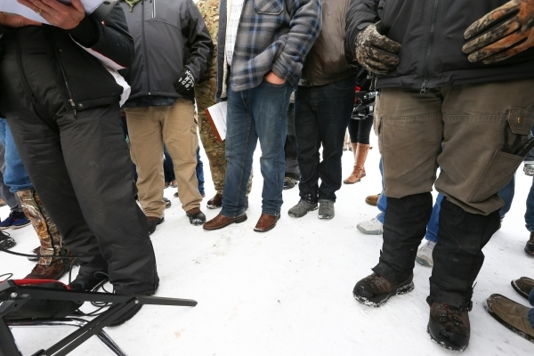 Ammon Bundy, center, stands as Shawna Cox, far left, gives a statement to reporters at a news conference by the entrance of Malheur National Wildlife Refuge near Burns, Ore., on Monday, Jan. 4, 20 ...