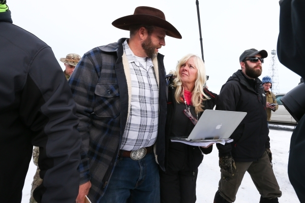 Ammon Bundy, with Shawna Cox, of Utah, arrives to speak with reporters at a news conference by the entrance of Malheur National Wildlife Refuge near Burns, Ore., on Monday, Jan. 4, 2016. Bundy, th ...