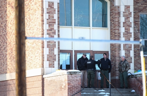 Law enforcement officers stand outside of Lincoln Junior High School before a statement from Harney County Sheriff Dave Ward in Burns, Ore. on Monday, Jan. 4, 2016. Law enforcement has set up at t ...