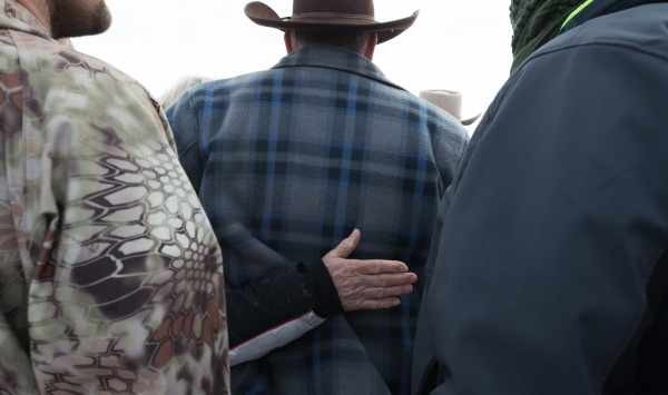 Ammon Bundy, center, is comforted by Shawna Cox as LaVoy Finicum, an Arizona rancher, not pictured, speaks with reporters at a news conference by the entrance of Malheur National Wildlife Refuge n ...