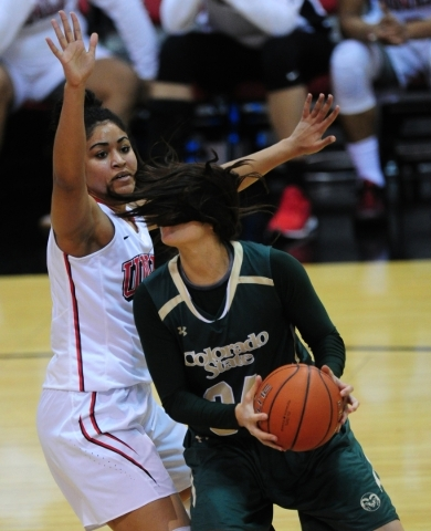 Colorado State forward Alana Arias (34) is blinded by her pony tail while driving to the basket in front of UNLV Rebels forward Paris Strawther (3) in the second quarter of their NCAA women' ...