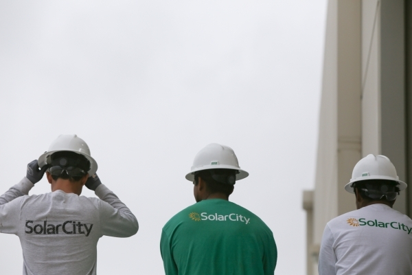 Workers take a break from dismantling teaching buildings in the SolarCity training facility in Las Vegas on Tuesday, Jan. 5, 2016. SolarCity decided to shutter its Nevada-based installation and sa ...
