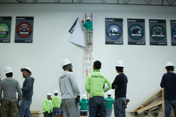 Workers watch as the banners celebrating SolarCity's installation crews across the U.S. are pulled down at the SolarCity training facility in Las Vegas on Tuesday, Jan. 5, 2016. SolarCity de ...
