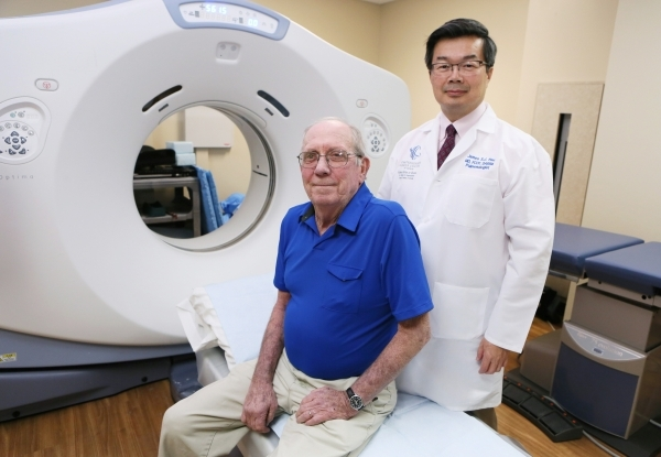 Patient Brian Fong, left, 67, who suffers from Chronic Obstructive Pulmonary Disease, and Dr. James Tsu, who specializes in pulmonary critical care medicine, are shown near a CT Optima 580 scannin ...