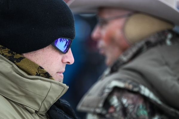 Arizona rancher and anti-government protestor LaVoy Finicum, right, speaks as a fellow protestor stands guard during a news conference at the Malheur National Wildlife Refuge headquarters, which t ...