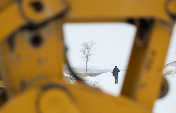 Anti-government protestor Michael Stettler of Christmas Valley, Ore. walks in the Malheur National Wildlife Refuge headquarters, which the group is occupying, near Burns, Ore. on Tuesday, Jan. 5,  ...