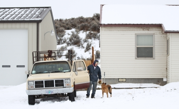 Anti-government protestor Michael Stettler of Christmas Valley, Ore. talks with his dog Volffie by a building at Malheur National Wildlife Refuge headquarters, which the group is occupying, near B ...