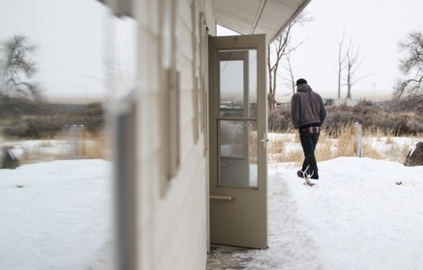 An anti-government protestor walks by a building at the Malheur National Wildlife Refuge headquarters, which the group is occupying, near Burns, Ore. on Tuesday, Jan. 5, 2016. The protestors, many ...