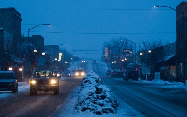 Traffic passes by on Broadway Avenue in downtown Burns, Ore. as snow falls on Tuesday, Jan. 5, 2016. Anti-government protestors have taken over the Malheur National Wildlife Refuge headquarters, a ...