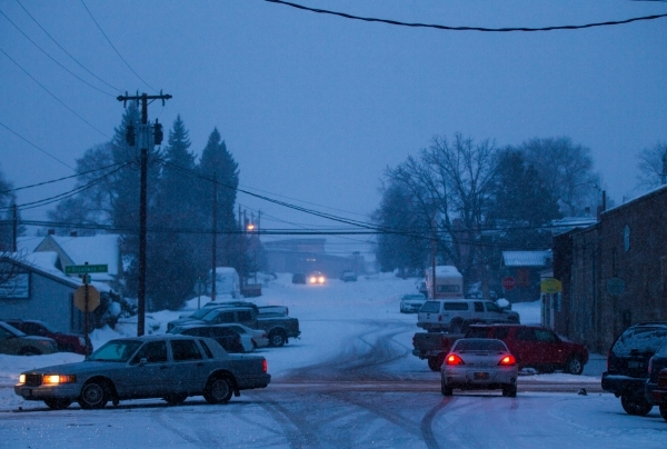 Traffic passes by on Adams Street and Broadway Avenue in downtown Burns, Ore. as snow falls on Tuesday, Jan. 5, 2016. Anti-government protestors have taken over the Malheur National Wildlife Refug ...