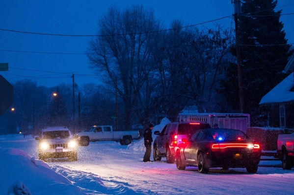 A motorist is pulled over by police officers in Burns, Ore. as snow falls on Tuesday, Jan. 5, 2016. Anti-government protestors have taken over the Malheur National Wildlife Refuge headquarters, ab ...