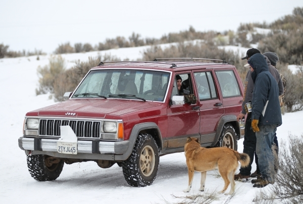 Anti-government protestors confer while standing guard by the entrance of the Malheur National Wildlife Refuge headquarters, which they are occupying, near Burns, Ore. on Tuesday, Jan. 5, 2016. Th ...