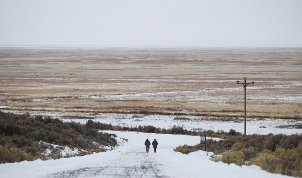 Anti-government protestors walk along a road at the Malheur National Wildlife Refuge headquarters, which they are occupying, near Burns, Ore. on Tuesday, Jan. 5, 2016. The protestors, many of them ...
