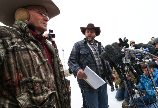Ammon Bundy, right, motions to Arizona Rancher LaVoy Finicum, left, while speaking with reporters at a news conference by the entrance of Malheur National Wildlife Refuge headquarters near Burns,  ...